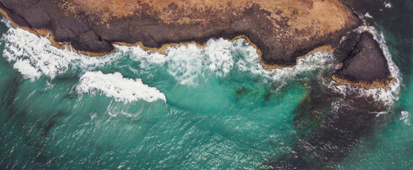 Aerial view of aqua sea waves breaking on rocky cliff, adventure summer travel vacation, perseverance and resilience concept, drone above view, World Oceans Day, reopen tourism concept