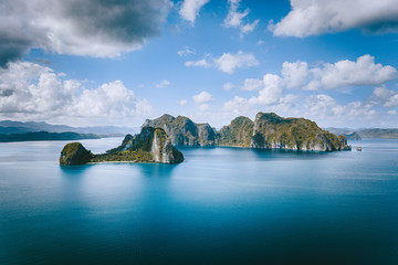 El Nido, Palawan, Philippines. Panoramic aerial view lonely tourist boat in open sea with exotic tropical Pinagbuyutan island standing out in ocean. Southeast Asia Bacuit archipelago