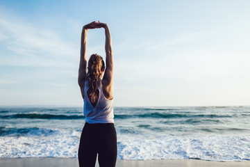 Healthy peaceful woman stretching arms at seaside