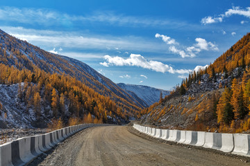 Gravel road with white and black fence in Siberian mountains with snow and yellow trees