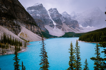Beautiful turquoise waters of the Moraine lake with snow-covered rocky mountains in Banff National Park of Canada