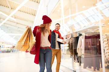 Cheery young good looking caucasian couple going Christmas shopping in a shopping mall. Girlfriend is carrying shopping bags and boyfriend is holding a Christmas gift. They're passing by shop window.