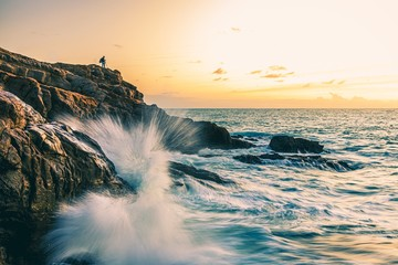 Hiking person on top of a rocky hill near the sea with crazy sea waves crashing
