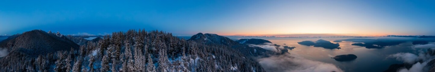 Aerial Panoramic View of Canadian Mountain Landscape on the Pacific Ocean Coast during a colorful sunset. Taken in Howe Sound near Vancouver, British Columbia, Canada.