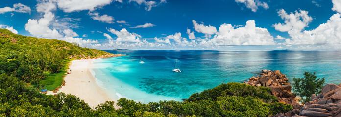 Widok z lotu ptaka Pano z plaży Grand Anse na wyspie La Digue na Seszelach. Biała piaszczysta plaża z błękitną laguną oceaniczną i zacumowanym jachtem katamaranem