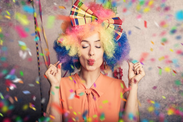 Englisch  beautiful young woman with colorful afro wig and colorful carnival make-up and confetti