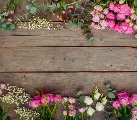 Frame of flowers on rustic wooden background with copy space