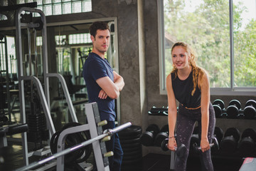 Fitness Trainer is controlling the training of the young women athletes. Athlete fitness exercises in the gym concept.