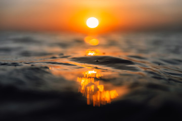 Sunset and waves in ocean. Warmy water texture with bokeh
