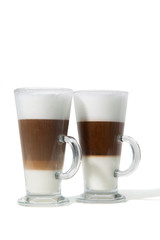 Two classes of caffe with milk on white background