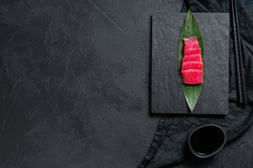 sashimi tuna on a stone Board. Black background. Top view. Space for text