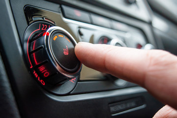 Button for heating the car seats close-up. The male hand presses the button for heating the seats of the car.