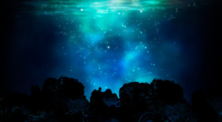 The depths of the sun through the water, the underwater world, the sea floor. Marine underwater landscape. Stones, corals, neon glow, reflection on the water. Night view.