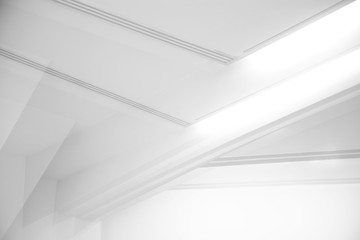 Ceiling and glowing girders with lamps. Abstract architecture fragment. Modern office building interior with triangular white concrete elements. Diagonal geometric composition in light gray halftones.