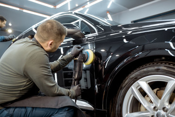 Two workers polishing vehicle body with special grinder and wax from scratches at the car service station. Professional car detailing and maintenance concept