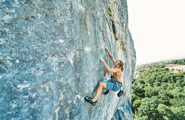 muscular man rockclimber with naked torso climbing on tough sport route. outdoors rock climbing and active lifestyle concept, climbing moments