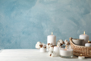 Burning candles, basket and cotton on white wooden table, space for text