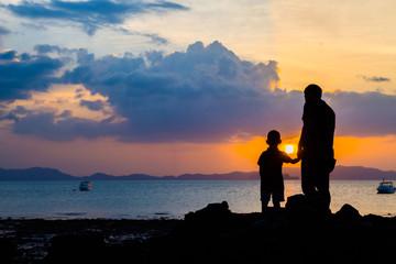 Sylwetka wizerunek ojciec i syn przy plażą