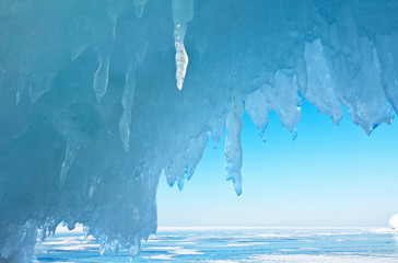 Winter Baikal Lake. Thick blue ice and icicles on the coastal rocks of Olkhon Island sunny cold day. Beautiful natural blue background