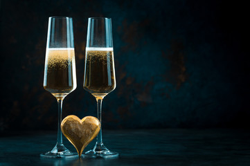 Two elegant romantic glasses with sparkling golden champagne with golden heart against a dark blue background. Valentine's day.