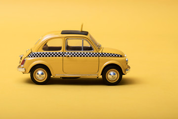 Yellow retro toy taxi on yellow background