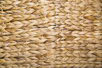 Background braided algae hyacinth yellow-brown with a beautiful weave in the form of braids. Backgrounds, design, structures.