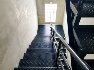Black Diamond steel floor stair material inside of the industrial building. duarable material choice for heavy use. Emergency exit walk way out from inside building area. Standard safety protocal.