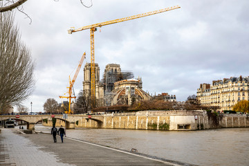 Paris, France - December 22, 2019: View of cranes and scaffoldings on the Notre Dame de Paris cathedral on the Ile de la Cite in the center of Paris after it was damaged by a fire in April 2019