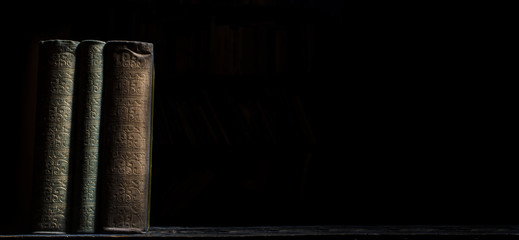 Old book on wooden bookshelf over black background. Vintage book covers still life on dark backdrop.