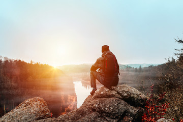 Young man in jacket, pants and backpack sitting on rock looking to river Vltava and valley in sunset.