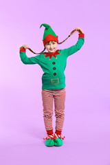Little girl in costume of elf on color background