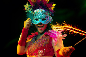 Beautiful young woman in carnival mask and stylish masquerade costume with feathers and sparklers in colorful lights on black background. Christmas, New Year, celebration. Festive time, dance, party.