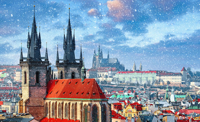 High spires towers of Tyn church in Prague city (Church of Our Lady before Tyn cathedral) urban landscape panorama with red roofs of houses in old town and blue sky with snowfall and clouds.