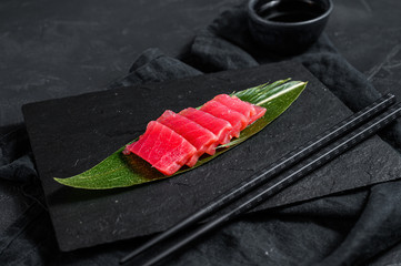 Fresh raw sashimi tuna on a stone Board. Black background. Top view