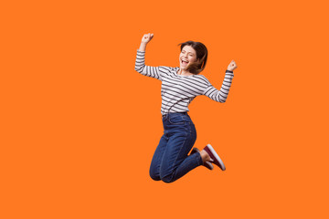 Full length portrait of excited pretty woman with brown hair in casual shirt and denim jumping celebrating victory, raising fists showing yes gesture. indoor studio shot isolated on orange background