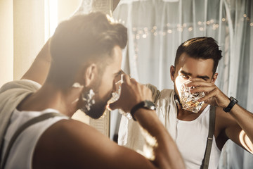 Handsome man with a glass of whiskey is looking in the mirror