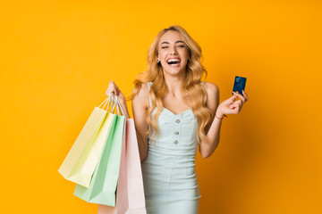 Seasonal sales. Excited woman holding credit card and bags