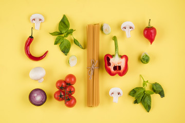 Italian cuisine concept. On a yellow background, a set of ingredients, pasta, tomatoes, peppers, mushrooms, basil
