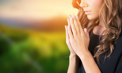 A young beautiful  girl praying on blurs background