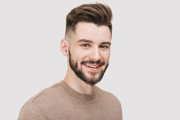 Closeup portrait of handsome smiling young man. Laughing joyful cheerful men studio shot. Isolated on gray background