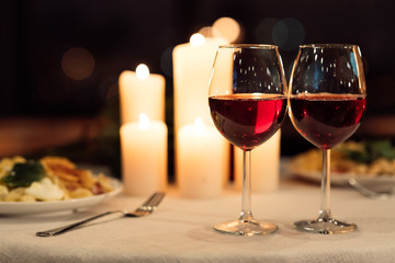 Two Glasses Of Red Wine Standing On Table With Candles