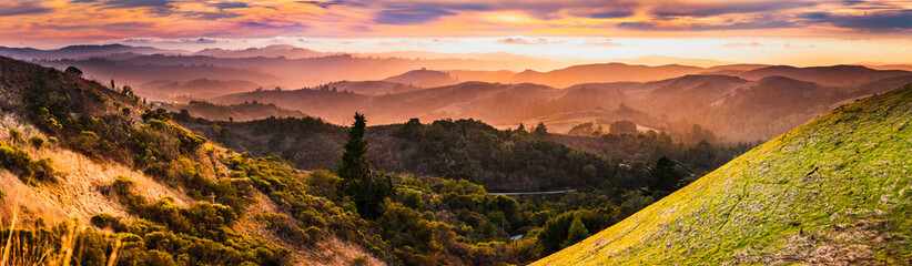 Expansive panorama in Santa Cruz mountains, with hills and valleys illuminated by the sunset light; San Francisco Bay Area, California