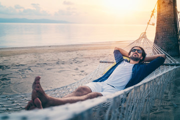 Young handsome Latin man in sunglasses relaxing in a hammock on the beach at sunset on the beach.
