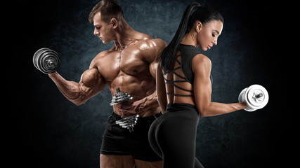 Sporty couple workout with dumbbells. Muscular man and woman showing muscles