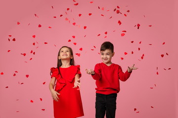 Happy romantic little couple child girl and boy stand in the rain of flying rose petals on pink background. St. Valentine's Day