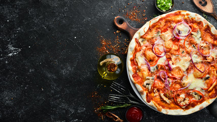 Homemade pizza on a black stone background. Italian cuisine. Top view. Free space for your text.