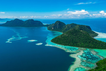 Amazing tropical paradise islands from air with blue turquoise blue lagoon water and coral reef. Aerial view of Bohey Dulang island panorama. Hawaii, Philippines, French polynesia.