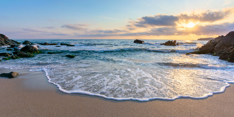 sunrise on the beach. beautiful summer scenery. rocks on the sand. calm waves on the water. clouds on the sky. wide panoramic view