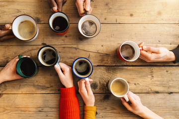 Friends group drinking coffee and cappuccino in a bar or restaurant - People hands cheering and toasting on top view point - breakfast together concept with white and black men and women