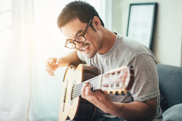 artist playing acoustic guitar,sing folk song.happy man sitting enjoy on sofa in relax time.concept for art and music therapy for relaxation and healing for people
